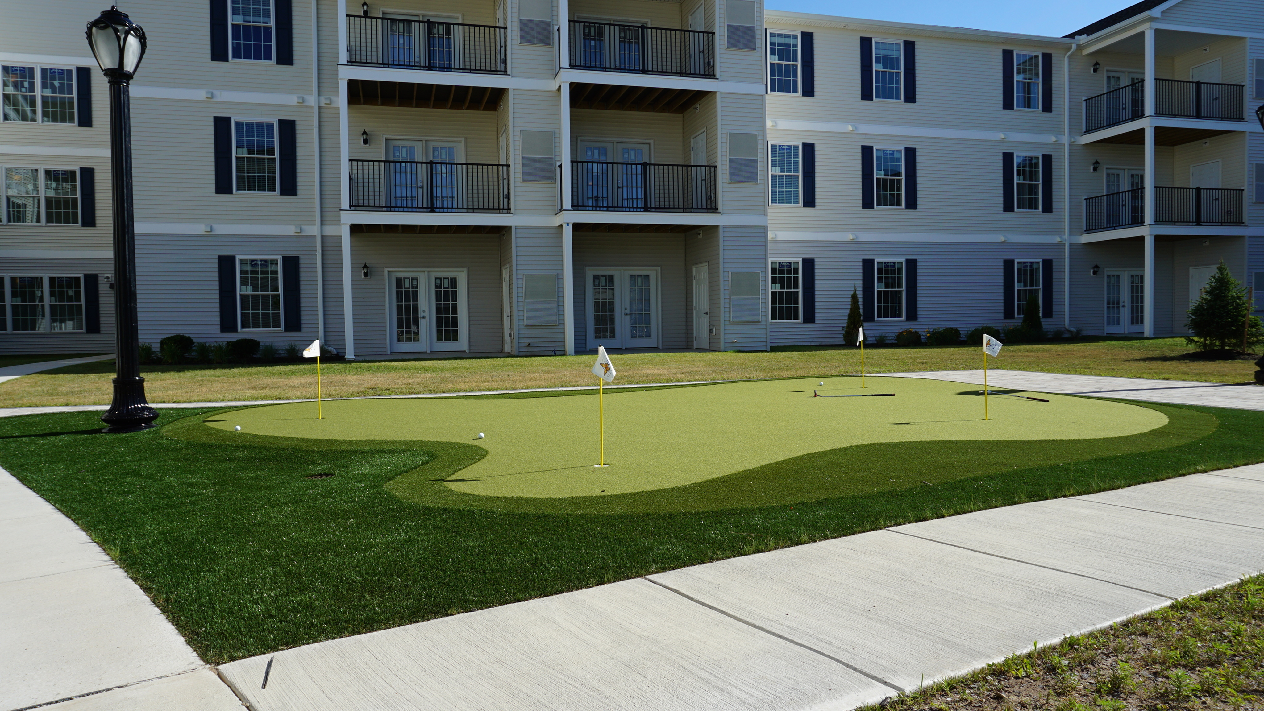 The Belvedere Apartments, exterior, outdoor putting green, building view with balconies, walkways, street lamp