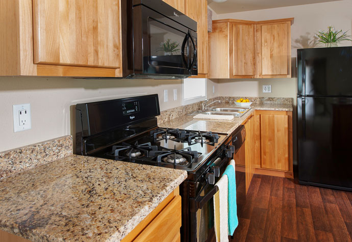 picture of apartment kitchen marble counter built in microwave stove refrigerator dishwasher