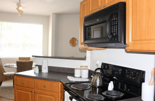 Kitchens feature paneled cabinets, black appliances and handsome plank floors