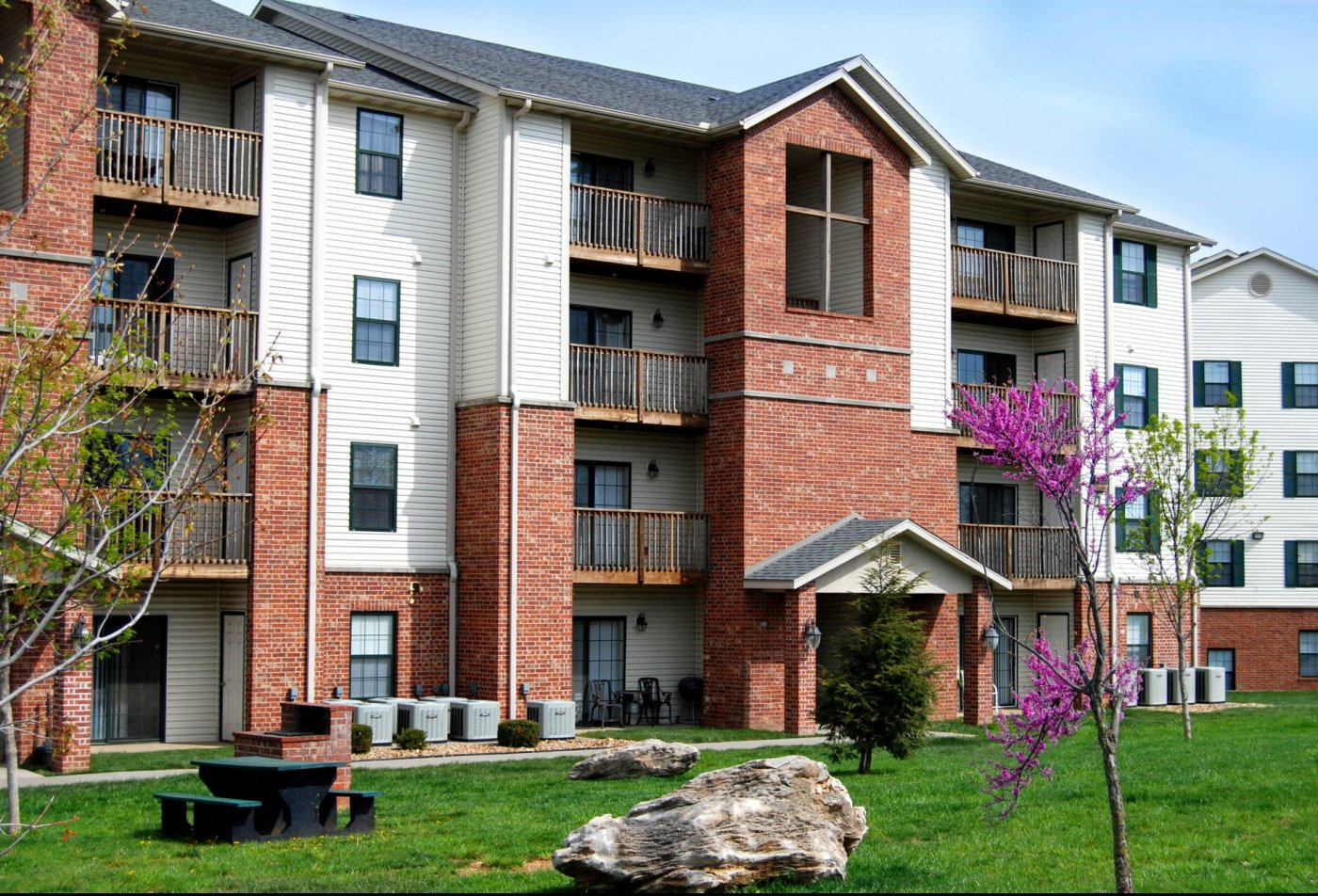 Exterior of Apartment complex with lush landscaping and barbecue stations