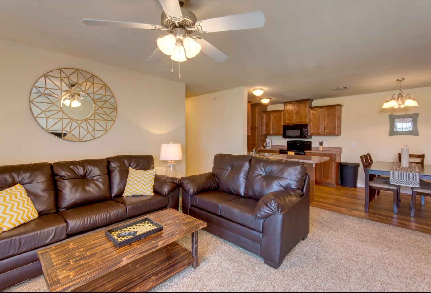 Furnished Apartment with modern furnishings and leather sofas. Living room view over looking the kitchen with oak cabinets and black appliances.