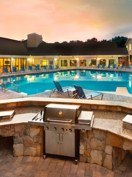 Community pool with grilling and cooking area and lounge chairs