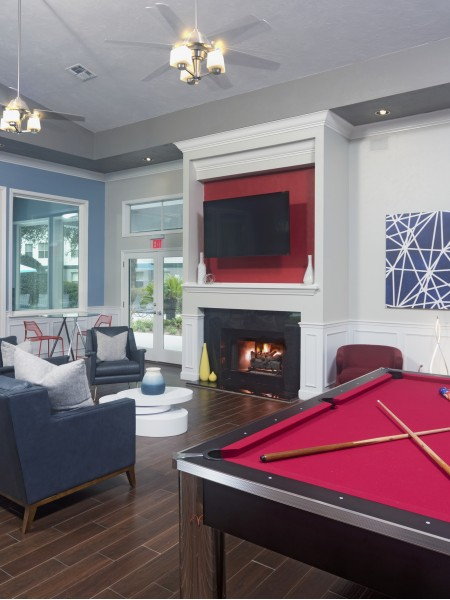 community clubhouse with seats, pool table, and a fireplace with a TV above it