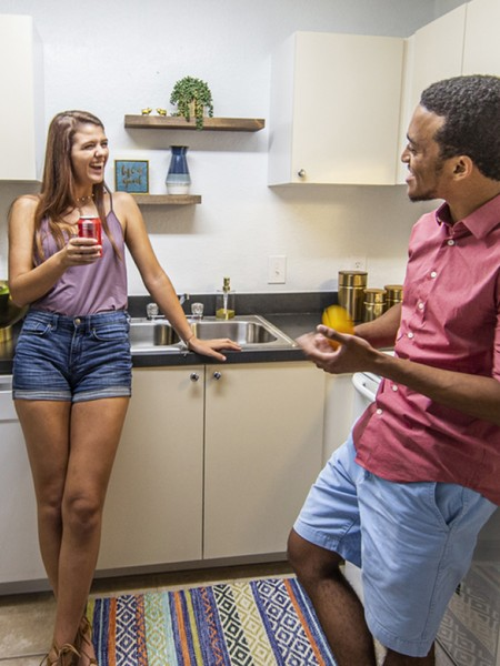 2 people talking to each other in a kitchen with white cabinets and black countertops