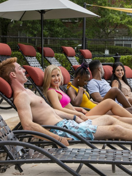 5 people laying on lounge chairs near community pool