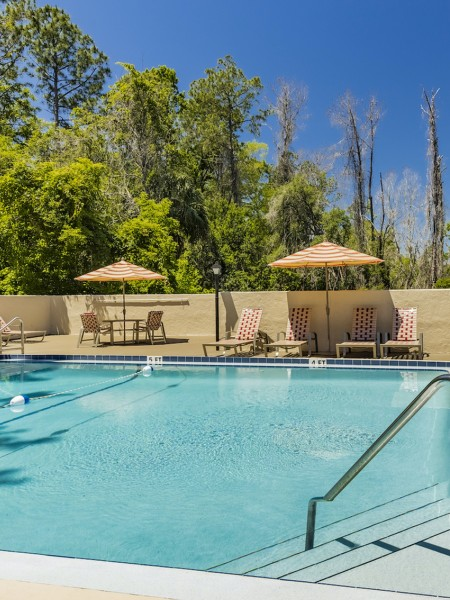 Community pool area with lounge seating, brick pavers, and trees in the background.