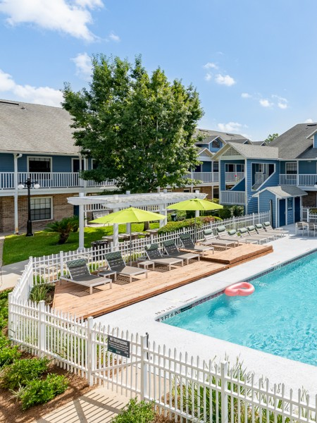 Second floor view of the courtyard and community pool. There is green space, lounge seating, and a fenced in pool.