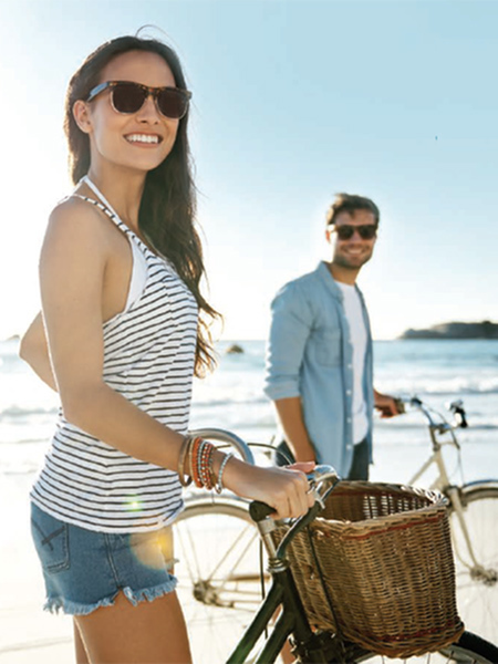 Man and woman with bikes at the beach.