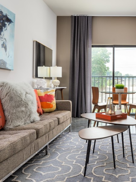 View of the Furnished Living Room at Cottonwood Westside Apartments, Showing Chairs, Tables, and Glass Sliding Door