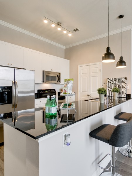 View of the Renovated Apartment Interior at McKinney Uptown Apartments, Showing Kitchen With Granite Counter Top and Stainless Steel Appliances