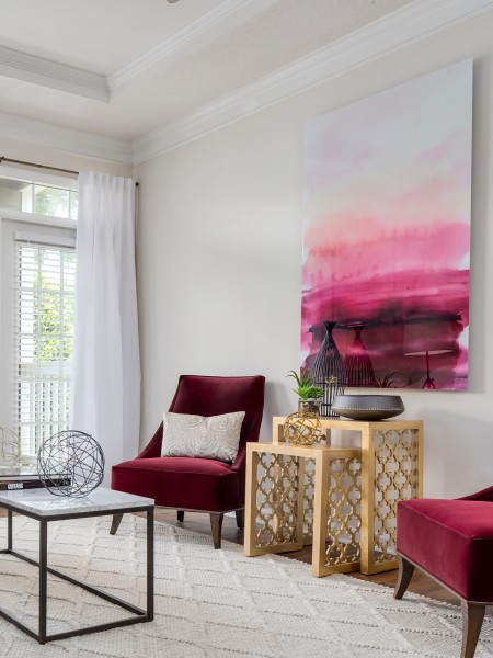 View of the Living Room at Retreat at Peachtree City Apartments, Showing Accent Chairs, Plank Wood Flooring, and Doors to Patio