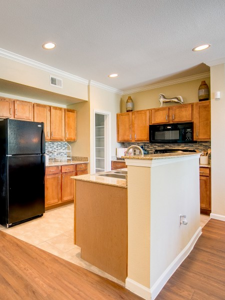 View of the Kitchen at Enclave on Golden Triangle Apartments, Showing Tile Flooring, Gas Appliances, Countertops, Backsplash, and Cabinetry