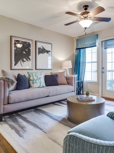 View of the Classic Apartment Interior at Midtown Crossing Apartments, Showing Furnished Living Room with Seating Area and Door to Attached Balcony