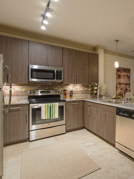 View of the Kitchen at Heights at Meridian Apartments, Showing Granite Countertop, Stainless Steel Appliances, and Tile Backsplash