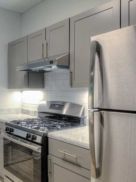 View of the Kitchen at Retreat at River Park Apartments, Showing Stainless Steel Appliances, Tile Backsplash, Countertops, and Cabinets
