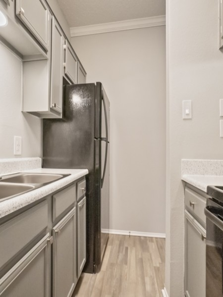 View of the Classic Apartment Interior at 4804 Haverwood Apartments, Showing Kitchen With Wood Plank Flooring and Gas Appliances