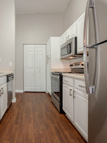 View of the Renovated Apartment Interior at Arbors at Fairview Apartments, Showing Kitchen With Plank-Wood Flooring and Stainless Steel Appliances