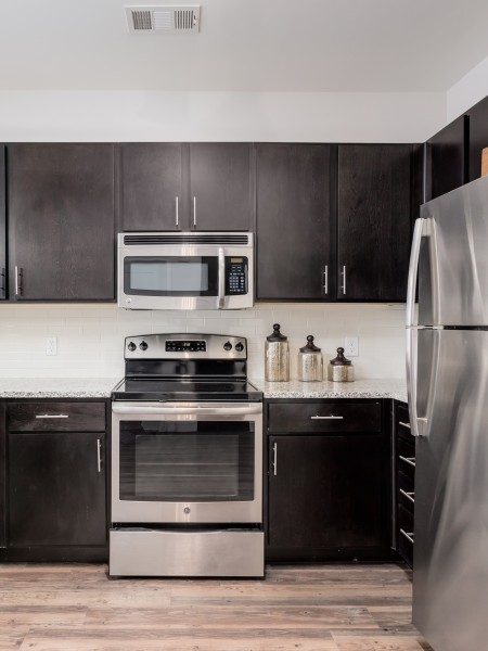 View of the Kitchen at The Melrose Apartments, Showing Plank Wood Flooring, Granite Counter Top, and Stainless Steel Appliances