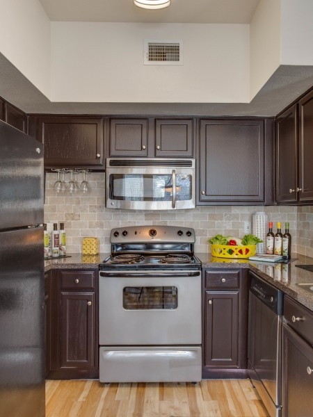 View of the Kitchen at The Raveneaux Apartments, Showing Plank Wood Flooring and Appliances