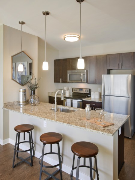 View of the Apartment Interior at Parc Westborough Apartments, Showing Stainless Steel Appliances, Bar Stools, and Granite Countertop