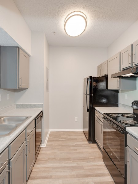 View of the Renovated Apartment Interior at Waterford Creek Apartments, Showing Kitchen with Gas Appliances and Plank Wood Flooring