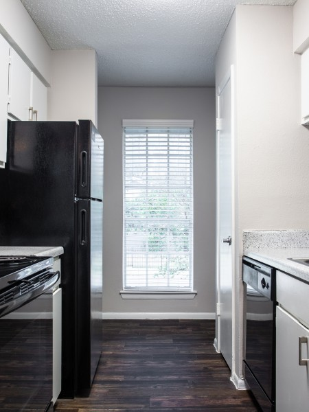 View of the Renovated Apartment Interior at Solara Apartments, Showing Kitchen With Electric Appliances, Plank Flooring, Cabinets and Countertops