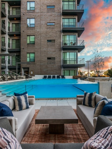View of the Sundeck at The Hudson Apartments, Showing Elevated Swimming Pool, Loungers, and Outdoor Furniture