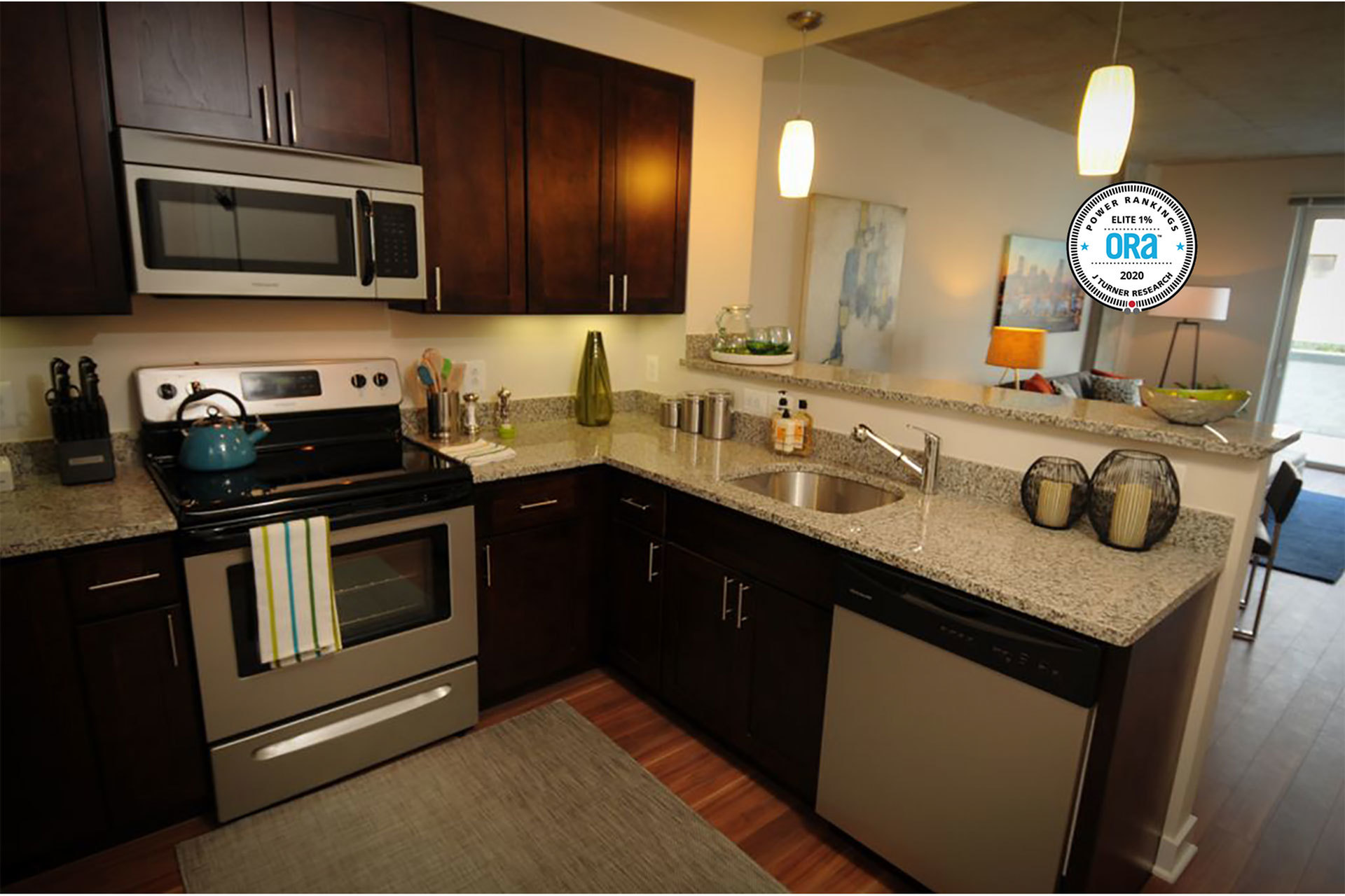 Kitchen with stainless steal appliances, granite counters, and a breakfast bar over looking the living space. ORA 2020 Power Rankings J Turner Research seal superimposed in the right corner of the photo.