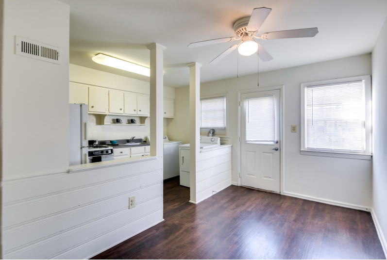 Kitchen view from dining room, white cabinets and hardwood flooring.