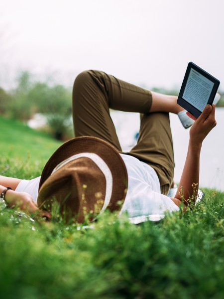 Man laying on grass looking up at e-reader