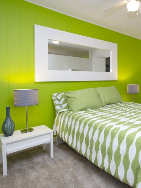 bedroom with green accent wall, 2 end table with lamps, and white framed mirror