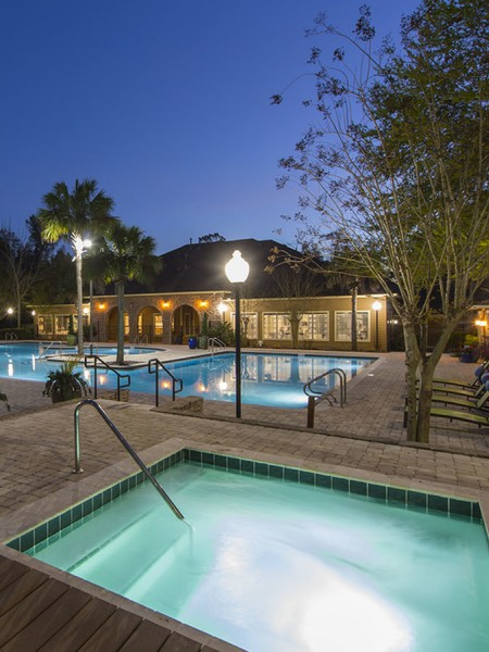 Dusk shot of the community jacuzzi as well as the community pool and clubhouse in the background.