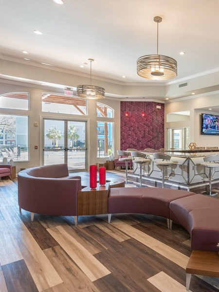 community clubhouse with s shaped couch, large windows and bar area
