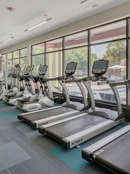 community gym treadmills with windows facing community pool