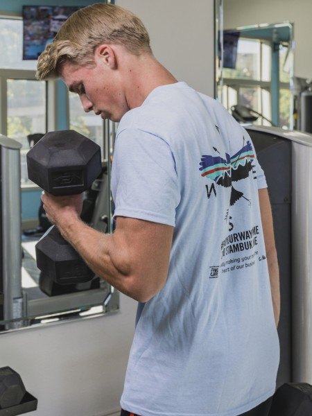 Young adult male working out with weights in front of mirror inside the community gym.