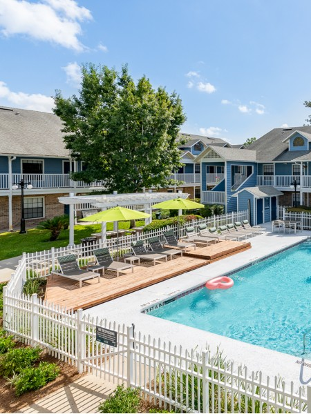 Community pool with grey lounge chairs, wooden deck, grass area, sidewalk and pergola