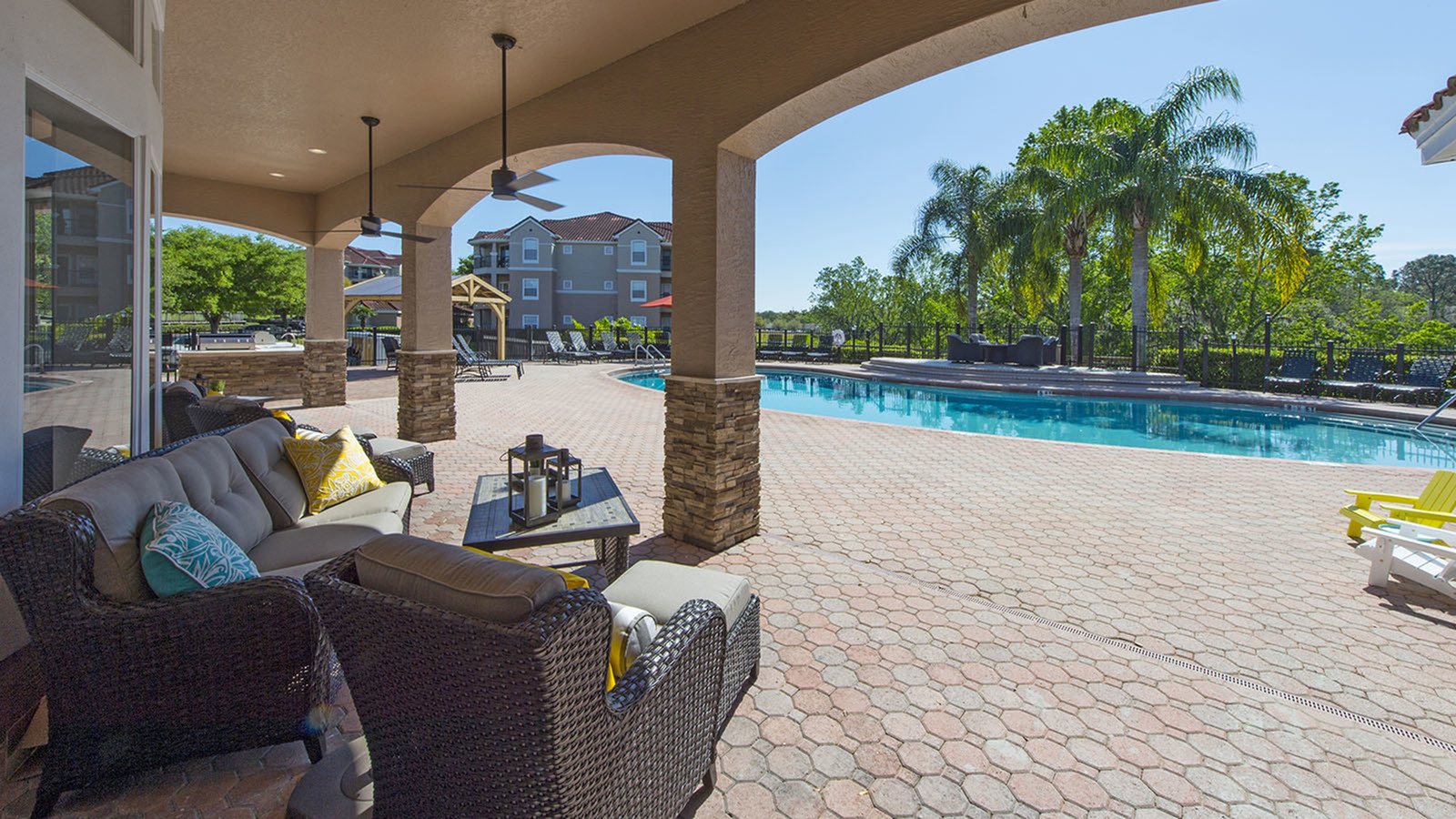 Outdoor patio furniture with pool and trees in background.