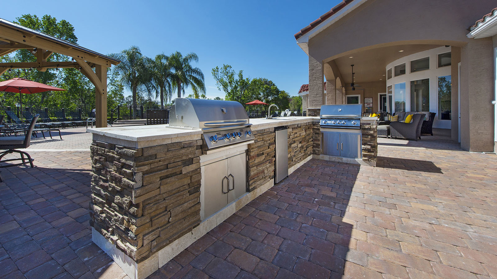 Outdoor grills on brick pavers. Trees and pool in background.