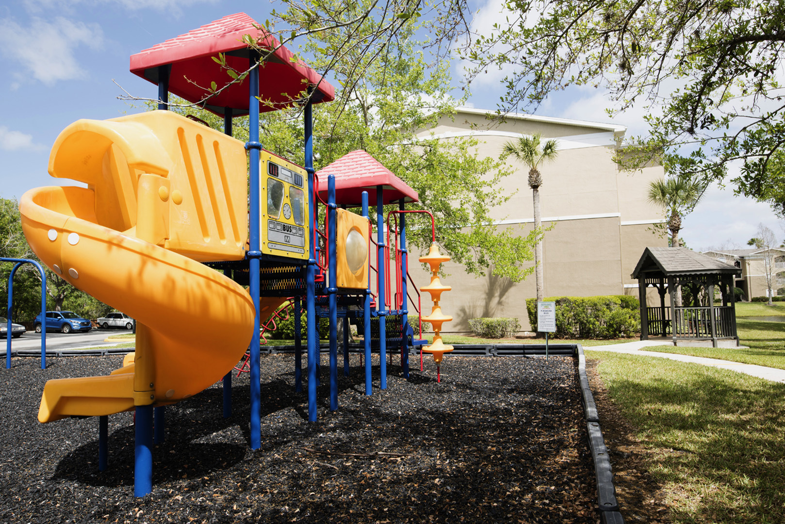 Children\'s playground surrounded by mulch and trees.