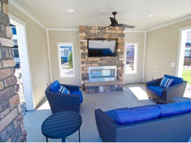 Pool cabana with 1 sofa, 2 chairs, flat screen television, and fireplace