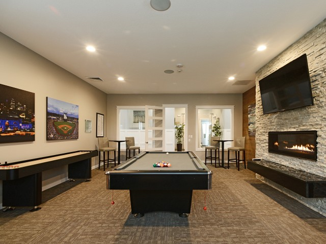 Game room with billiards table, shuffle board, flat screen television, fireplace, and 2 tables