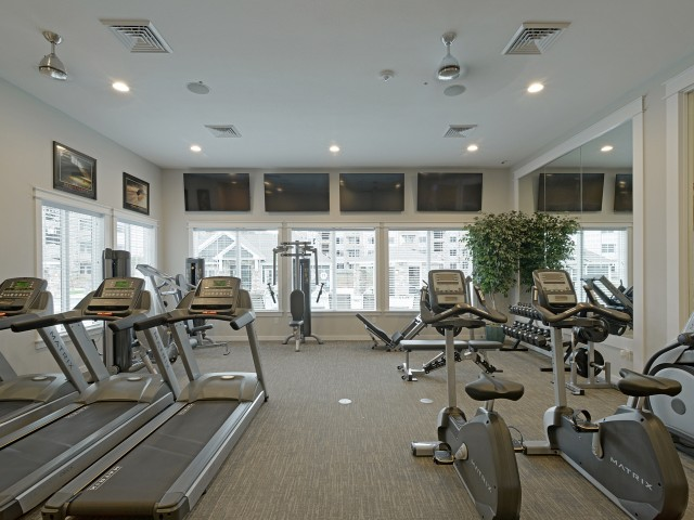 Fitness Center showing 3 treadmills, 2 stationary bikes, shoulder machine, tricep press machine, free weights, leg press, and 4 televisions