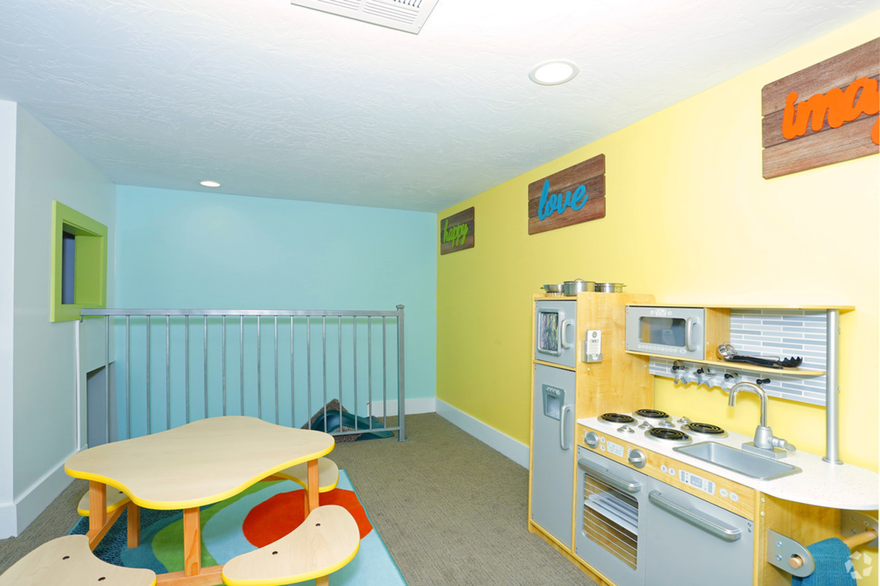 2 level play room shaped like a house with stairs, slide, play kitchen, television, and toy shelf