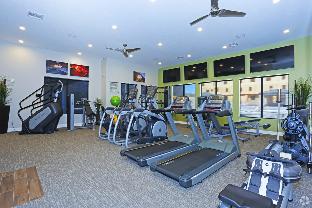 Fitness center with treadmills, ellipticals, stair stepper, rower, free weights, exercise balls and bands, and four televisions