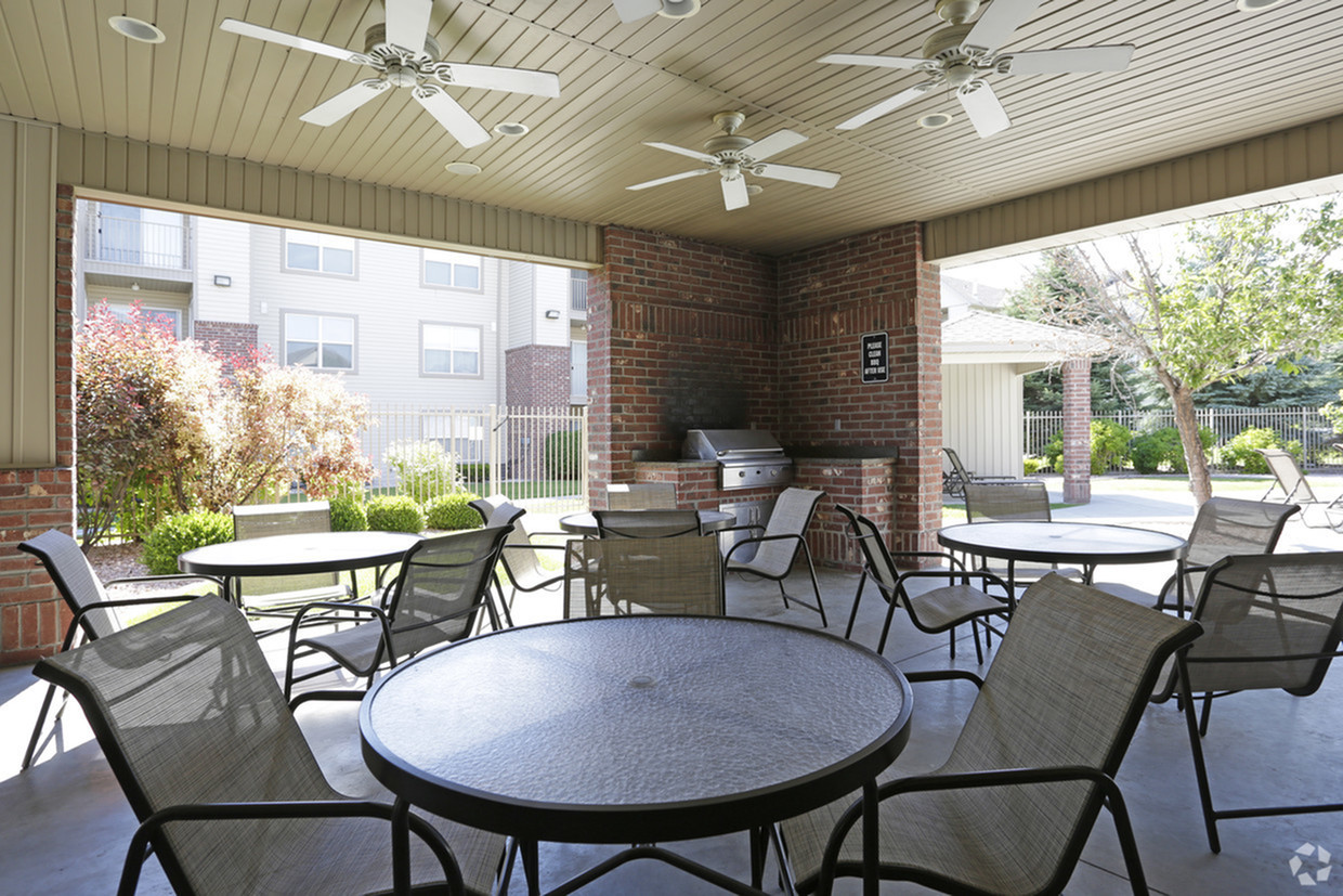 Barbecue area with 4 circular tables, 4 chairs around each, and 1 stainless steel grill