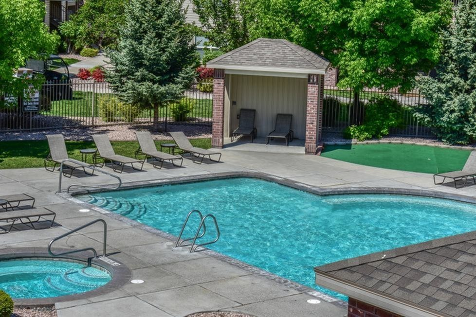 Community Swimming Pool surrounded by 10 tanning chairs and pool cabanas