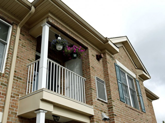 Balcony of a Heritage Court apartment features white railing and entry to a utility closet. Flowers are also hung on the balcony.