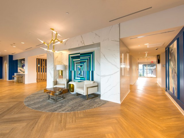 Image of Elegant reception lounge featuring marble paneling, modern gold light fixtures & herringbone hardwood flooring for The Cabochon at River Oaks Apartments