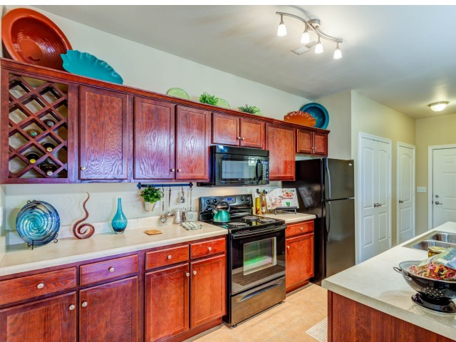 Image of Abundant Cherry Finish Cabinetry with Wine Rack for Autumn Breeze Apartments