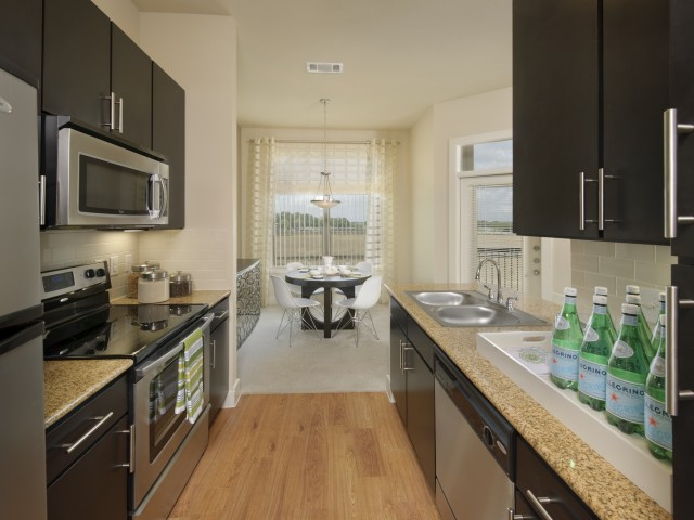 Image of Elegant Granite Countertops with Tiled Back Splashes for Voyager at Space Center Apartments